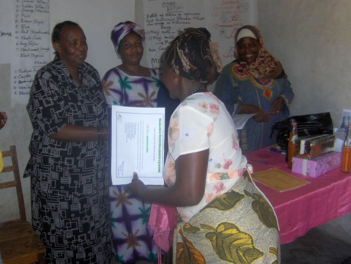 helping-widows-with-aids-in-Tanzania-handing-out-certifications.